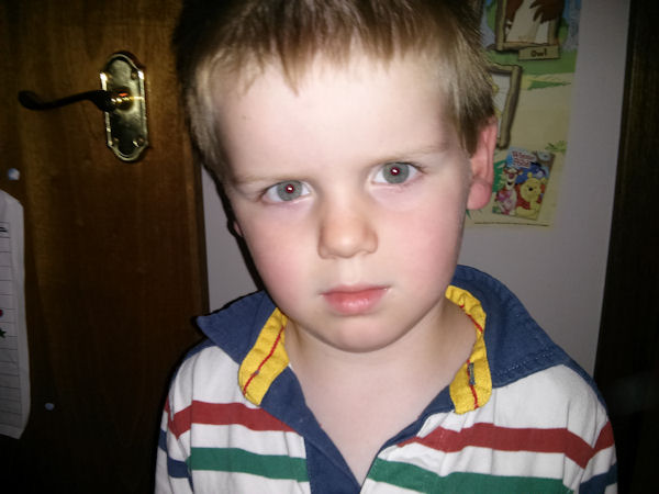 A very serious looking Isaac, aged 3 wearing a striped rugby shirt.