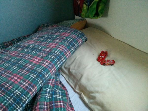 Two red Lightning McQueen toy cars under Isaac's pillow.