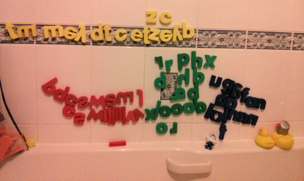 Foam bath letters on the tiled wall.