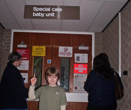 Benjamin pointing to a sign that reads: Baby Special Care Unit