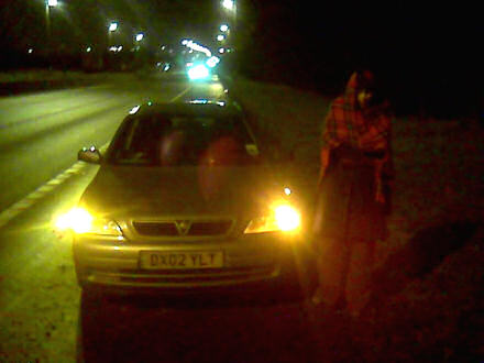 Jane wrapped in a travelling rug standing beside our broken down Astra