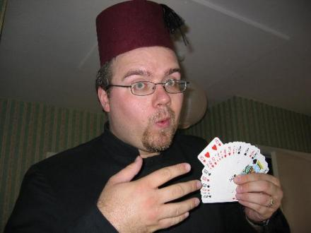 Gareth wearing a fez -- a red, felt hat -- doing a magic trick with cards.