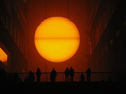 Photo called Weather Project which shows people standing in front of a huge sun.