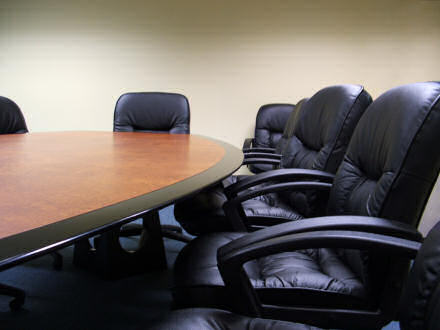 Leather chairs arranged around a board room meeting table