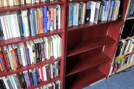 Photograph of two bookcases, one on the left has 3 empty shelves