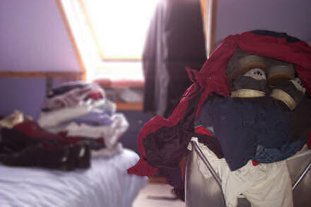 A pile of clothes lying on a bed, and an over-stuffed laundry basket. Three suits hang by the window.