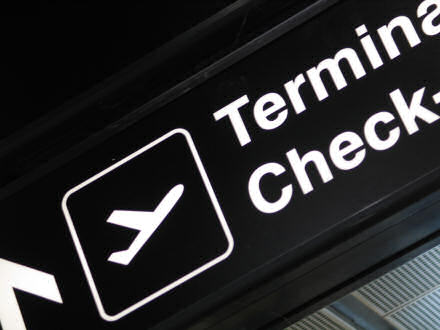 Terminal sign showing an airplane taking off and the words Terminal Check-in