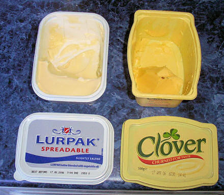 A tub of Lurpak spreadable margarine on the left, Clover on the right.