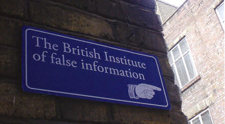Sign reading The British Institute of false information, with a hand pointing right, round a corner.