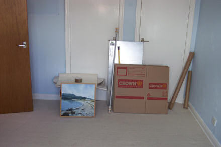 An almost empty dining room.  A few boxes and a painting lie up against a door.