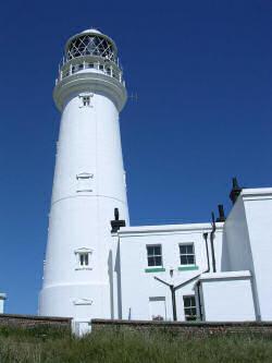 White lighthouse against a deep blue sky.