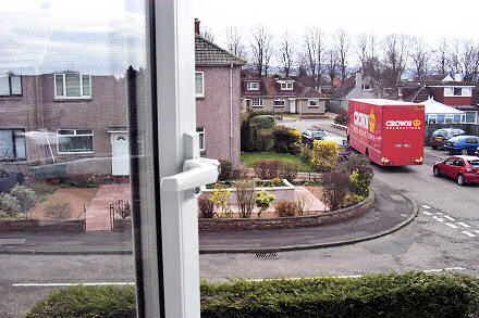 View out of an upper window of a Crown removals lorry driving away.