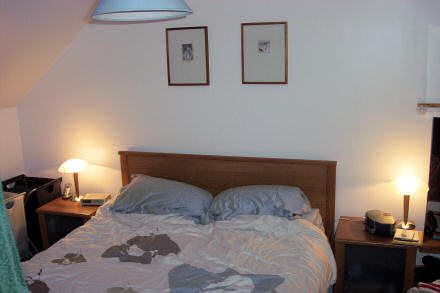 Photograph of our new bedroom.  A kingsize bed sits beneath two paintings.