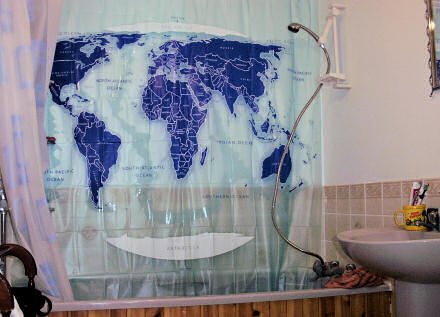 Bath and shower with a shower curtain showing a map of the world.