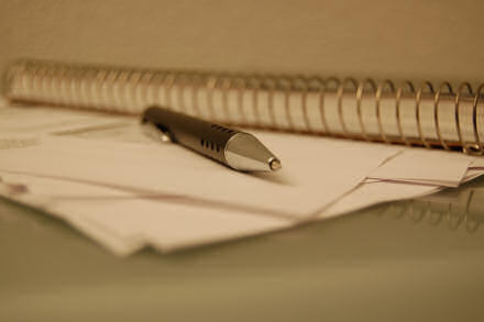 A ball-point pen lying next to a ring-bound notebook.