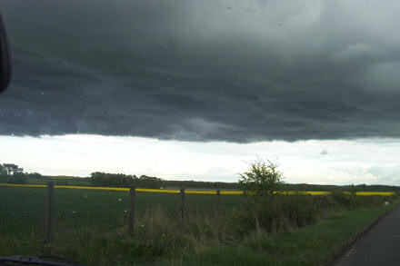 Dark rain clouds over green and yellow fields.
