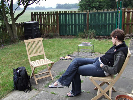 Jane sitting on a wooden chair in the garden, a barbeque is in the background.