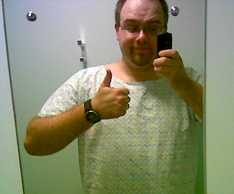 Gareth wearing a hospital gown, giving the thumbs up sign.