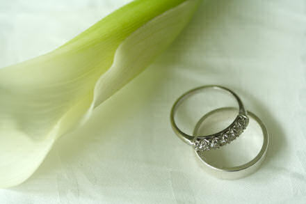 Wedding rings beside a lily.