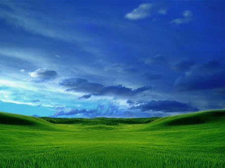 Rolling green hills, with a blue, cloudy sky overhead.