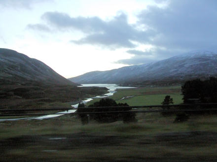 Photograph of highlands scene. River winds between two hills.
