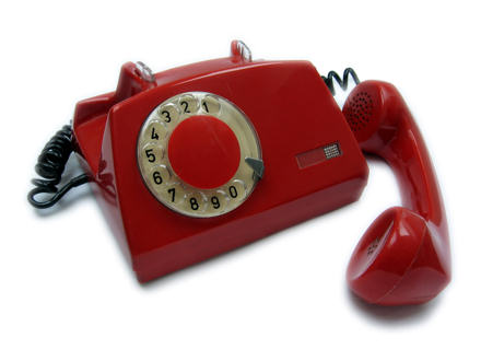 Old red telephone with the receiver off the hook.