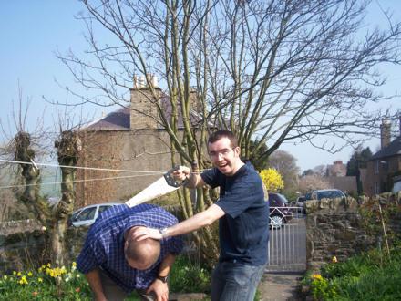 Eddie sawing off Gareth's head in the garden.