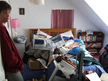 Jane looking worried by the pile of stuff on the bed.
