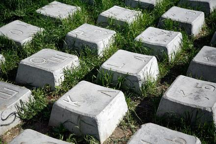 Large concrete Russian keyboard keys on grass