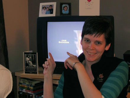 Jane Saunders pointing to her name on the TV