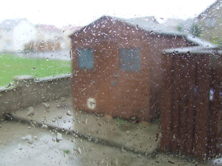 Close-up of rain on a window, with a shed in the background.