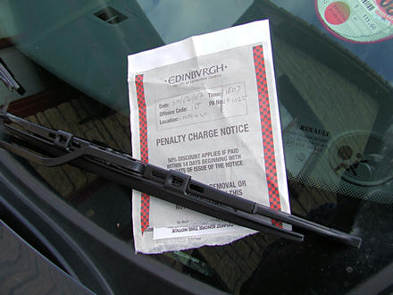 Penalty charge notice beneath windscreen wiper blade