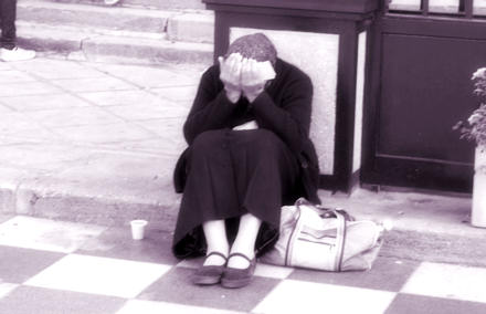 Woman sitting on the pavement crying into her hands.