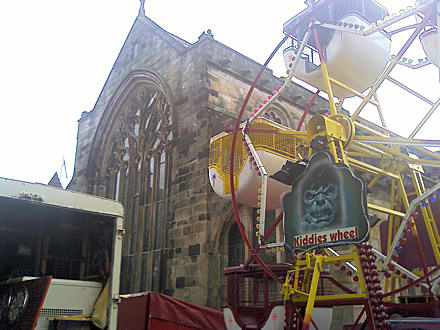 Small ferris wheel beside church building.