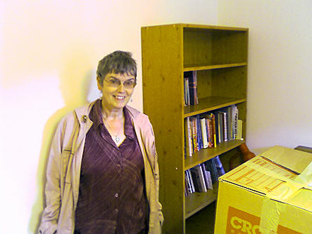 Mum standing beside a bookcase