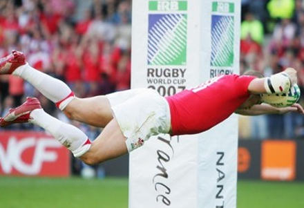 Welsh rugby player flying over the line
