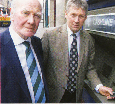 Sir Menzies Campbell with man not using cashline machine properly.