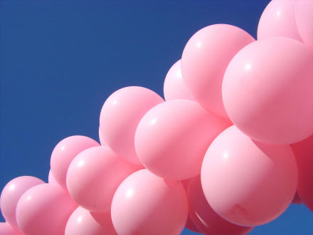 Pink balloons against a deep blue sky.