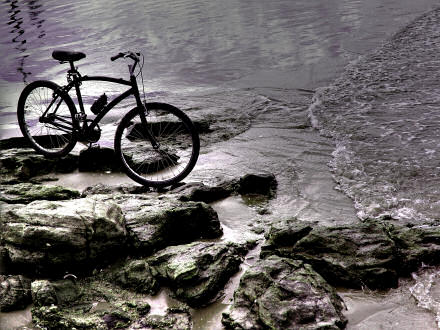 A bicycle on rocks beside some water.