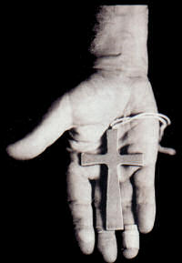 Black Sabbath drummer, Bill Ward's hand, holding a cross.