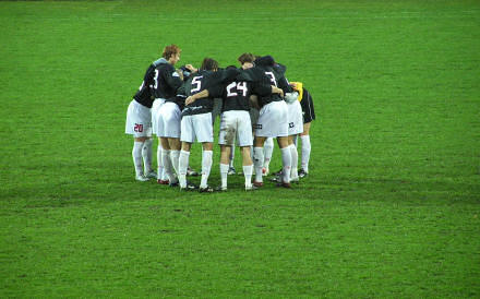 Footballers huddled on a pitch.