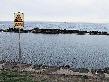 Looking out to sea, a danger sign in the foreground.