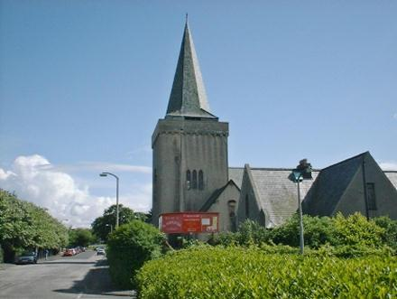 St Salvador\'s Church in Stenhouse, Edinburgh. A grey building with a tower and spire, and blue skies behind.
