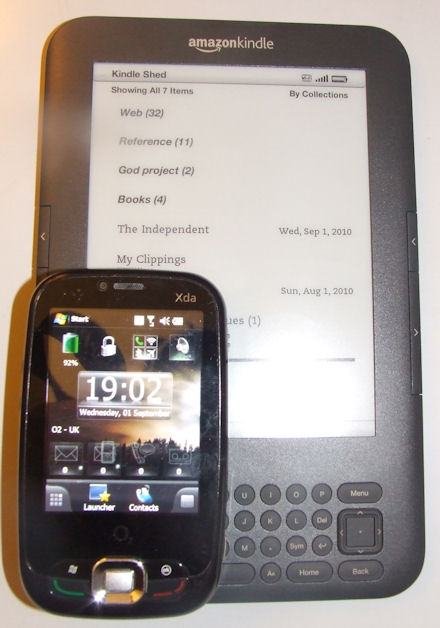 O2 Xda Zest phone sitting on top of an Amazon Kindle 3
