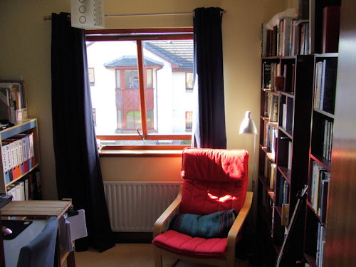 My study, looking towards the window, with chair and bookcases