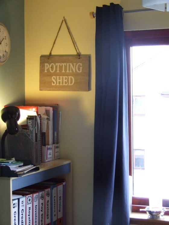 "Sign hanging on the wall that says ""Potting Shed""."