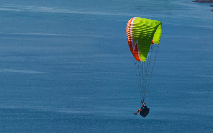 Paraglider in a rainbow-coloured parachute
