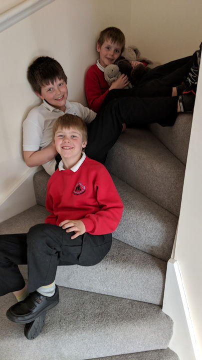 From top to bottom: Isaac, Reuben and Joshua, sitting on the stairs. They are all wearing school uniforms.