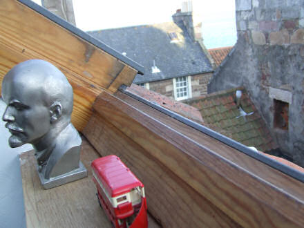 View out the back window, towards our cottage's roof. A Lenin bust and London bus in foreground.